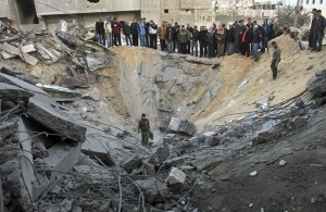 28 December: Palestinians gather in the crater left by an Israeli missile strike on a building used by Hamas in Gaza City - Photograph: Khalil Hamra/AP - The Guardian